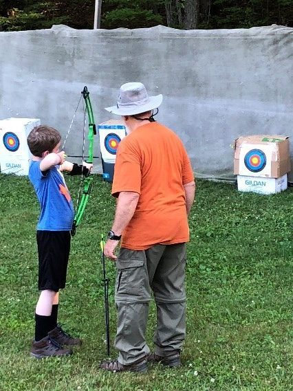 youth shooting arrow while Scouter coaches.