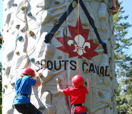 2 Scouts climbing on the climbing wall.